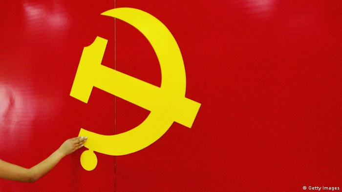 BEIJING - JUNE 15: An outstrected hand touches the Hammer and Sickle logo at an exhibition promoting the Chinese Communist Party on June 15, 2005 in Beijing, China. A senior official of the Communist Party of China (CPC) has urged officials in charge of discipline inspection and supervision to be fully aware of the vital importance of improving the Party's work style and building a clean government. (Photo by Guang Niu/Getty Images)