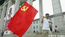 BEIJING - JUNE 28: A man holding a Chinese Communist Party flag walks out of an exhibition held by the government to mark the upcoming Communist Party of China's 85th Birthday on June 28, 2006 in Beijing, China. China celebrates CPC's Birthday on July 1 each year and party membership has grown to 70.8 million according to the latest statistics of the party. (Photo by Guang Niu/Getty Images)