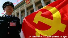 A Chinese policeman holds a Chinese Communist Party flag to show his supports to the party during the 17th Communist Party Congress in Beijing 15 October 2007. Chinese President Hu Jintao ended a long speech on 15 October outlining the Communist Party's performance and its major priorities for the economy, environment, military, Taiwan and social issues. AFP PHOTO/TEH ENG KOON (Photo credit should read TEH ENG KOON/AFP/Getty Images)