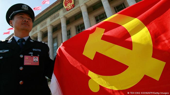 A Chinese policeman holds a Chinese Communist Party flag to show his supports to the party during the 17th Communist Party Congress in Beijing 15 October 2007. Photo: TEH ENG KOON/AFP/Getty Images)