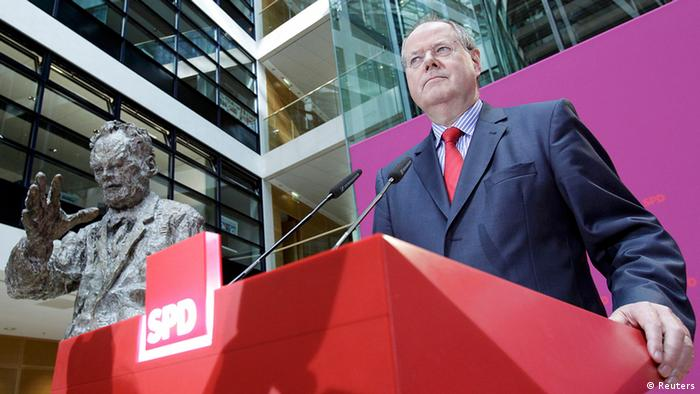 Former German finance minister Peer Steinbrueck stands beside a statue of Willy Brandt