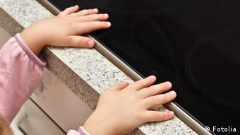 Ein Mädchen greift mit den Händen auf eine Herdplatte