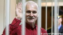 epa03013553 A Belarussian human rights activist Ales Bialiatski (also transliterated as Alex Belyatsky) waves from a cage in a court room during a court session in Minsk, Belarus, 24 November 2011. Ales Bialiatski is a leader of Viasna, a human rights group based in Minsk. He was arrested on 04 August 2011 and charged with tax evasion, after Polish and Lithuanian prosecutors gave Belorussian police information about Vesna's bank accounts in their countries. The court in Minsk on 24 November convicted him and gave him a four and a half year sentence in a maximum security jail. EPA/TATYANA ZENKOVICH