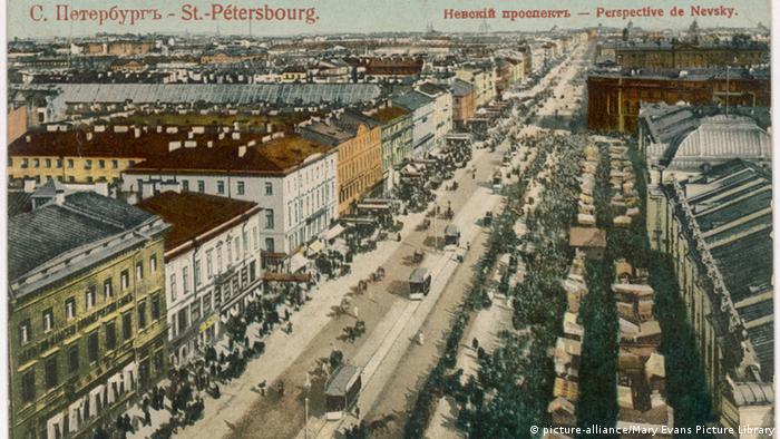 Cartão-postal antigo do centro de uma cidade com bondes em larga avenida e prédios dos dois lados