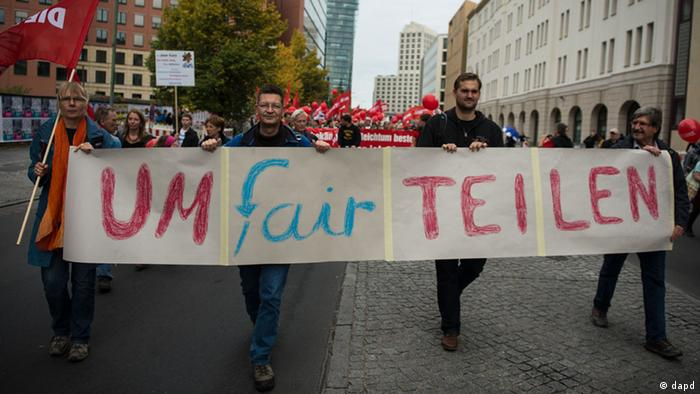 Protesters in Berlin hold up an umfairteilen banner protesting for a tax on the wealthy. (dapd)