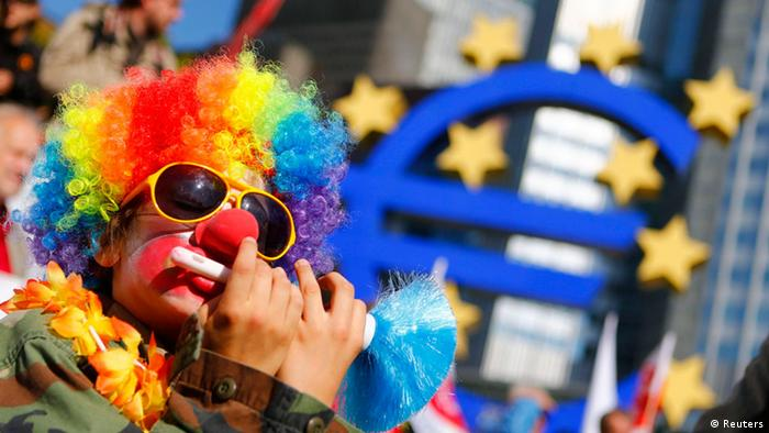 A demonstrator dressed as a clown sits next to the euro sculpture in front of the headquarters of the European Central Bank (ECB) during an anti-capitalism demonstration in Frankfurt, September 29, 2012. About 10,000 people took part in demonstrations against capitalism in different cities across Germany. REUTERS/Kai Pfaffenbach (GERMANY - Tags: CIVIL UNREST BUSINESS POLITICS)