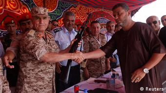 A Libyan man hands over his weapon to Libyan Army Chief of Staff Yussef al-Mangoush in Tripoli's Martyrs Square September 29, 2012. Hundreds of Libyans handed over weapons to the military in Tripoli and the eastern city of Benghazi as the authorities try to clean the streets from arms left over from last year's war. REUTERS/Ismail Zitouny (LIBYA - Tags: POLITICS MILITARY)