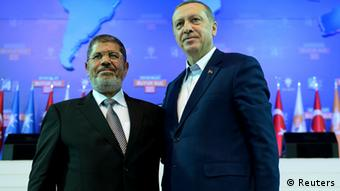 Turkey's Prime Minister and leader of ruling Justice and Development Party (AKP) Tayyip Erdogan (R) and his guest Egypt's President Mohamed Mursi greet the audience during AK Party congress in Ankara September 30, 2012. Photo: REUTERS/Kayhan Ozer/Prime Minister's Press Office/Handout