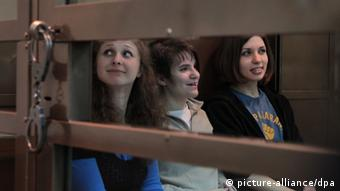 Maria Alyokhina (L), Yekaterina Samutsevich (C) and Nadezhda Tolokonnikova (R) sit in a glass-walled cage in the court room EPA/MAXIM SHIPENKOV