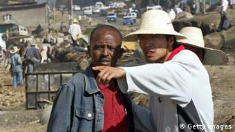 Addis Ababa, ETHIOPIA: A Chinese construction worker (R) supervises the building of a road in Addis Ababa, 27 April 2007. Ethiopian rebels holding seven Chinese oil workers captured during an attack this week on a Chinese oil venture in Ethiopia said 26 April they would release them 'as soon as possible'. AFP PHOTO/SIMON MAINA (Photo credit should read SIMON MAINA/AFP/Getty Images)