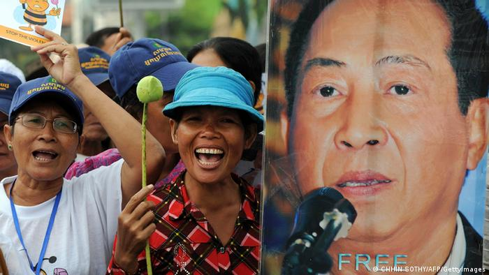 Cambodian protesters shout slogans next to a portrait of Mam Sonando (R), owner of the independent Beehive radio station, during a rally near the Phnom Penh municipal court on October 1, 2012. Photo: TANG CHHIN SOTHY/AFP/GettyImages