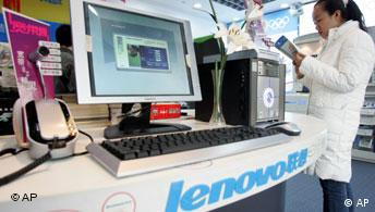A Chinese woman examines a pamphlet near Lenovo computers on display at a computer shop in Beijing, China, Wednesday, Dec. 8, 2004. China's biggest computer maker, Lenovo Group, said Wednesday it has acquired a majority stake in IBM Corp.'s personal computer business in a deal valued at US$1.75 billion (euro1.32 billion) _ one of the biggest Chinese overseas acquisitions ever. (AP Photo/Ng Han Guan)
