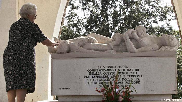 A woman touches a monument for the 560 victims of one of the worst Nazi wartime atrocities in Italy in the Tuscan village of Sant'Anna di Stazzema. AFP PHOTO (Photo credit should read -/AFP/Getty Images)