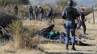 Police surround miners killed during clashes between protesting miners and police near a platinum mine in Marikana on August 16, 2012. An illegal strike at a South African platinum mine run by leading global producer Lonmin claimed more lives Thursday as police clashed with miners armed with machetes in the most violent day of the weeklong standoff. Ten people, including two police, had already been killed since workers began their strike on August 10. AFP PHOTO / STRINGER (Photo credit should read -/AFP/GettyImages)