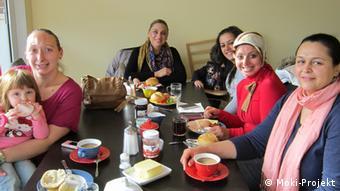 Kinder und Mütter an einem Frühstückstisch im Moki-Café (Foto: Moki-Projekt)