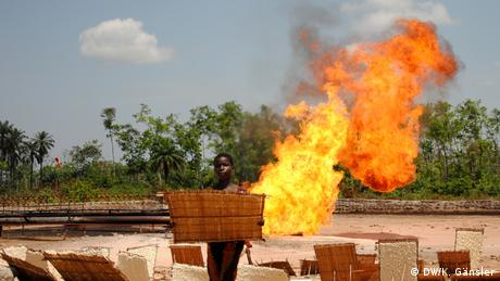 Young Nigerian carrying item next to gas flare