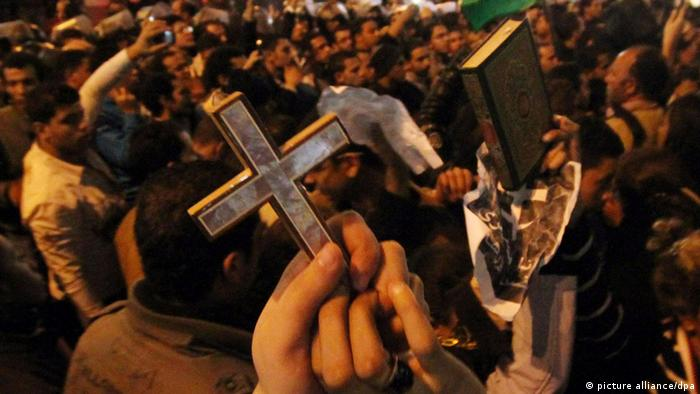 Egyptian Muslims and Christians raise the Quran and Cross