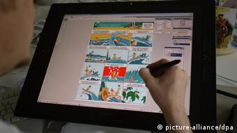 A hand on a computer screen that shows a comic (photo: Julia Rudorf/dpa)