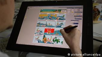 A hand on a computer screen that shows a comic (photo: Julia Rudorf/dpa)
