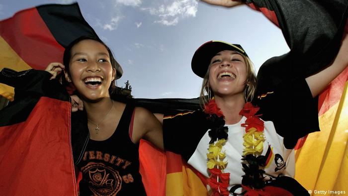 STUTTGART, GERMANY - JULY 08: German football supporters cheer at a public viewing area prior to their teams match on July 8, 2006 in Stuttgart, Germany. Germany faces Portugal in their FIFA World Cup 2006 third-round play-off football match in Stuttgart. (Photo by Ralph Orlowski/Getty Images)