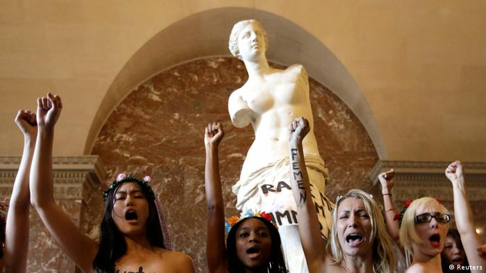 Members from the topless women's rights group Femen, with messages written on their chests, stage an action in front of the Venus de Milo statue at the Louvre Museum in Paris, October 3, 2012. The Femen activists were protesting charges of indecency filed against a woman raped by two Tunisian police officers. REUTERS/Philippe Wojazer (FRANCE - Tags: SOCIETY CRIME LAW) TEMPLATE OUT