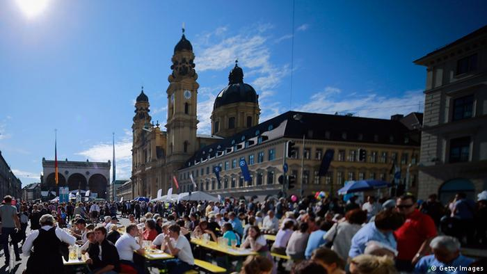 MUNICH, GERMANY - OCTOBER 03: (EDITOR'S NOTE: Image was created with a tilt shift lens) Revellers gather in the city center to celebrate German Unity Day (Tag der Deutschen Einheit) on October 3, 2012 in Munich, Germany. The event marks the day in 1991 when West Germany and East Germany reunited following the end of the Cold War. The main celebration is held every year in a different major city in Germany. (Photo by Johannes Simon/Getty Images)