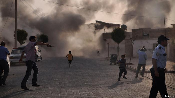 Smoke rises over the streets after an mortar bomb from Syria lands in Akcakale.