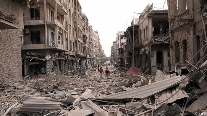 Syrian men walk at a street between destroyed buildings (photo: AP Photo/SANA)