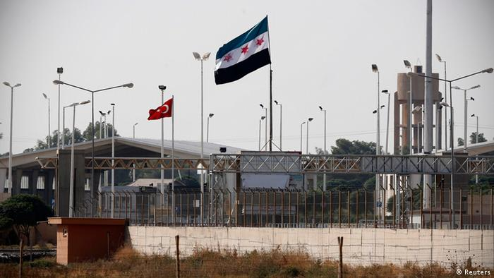Turkish and Syrian Independence flags are seen between the border gates Akcakale of Turkey and Tel Abyad of Syria, Photo: REUTERS/Murad Sezer