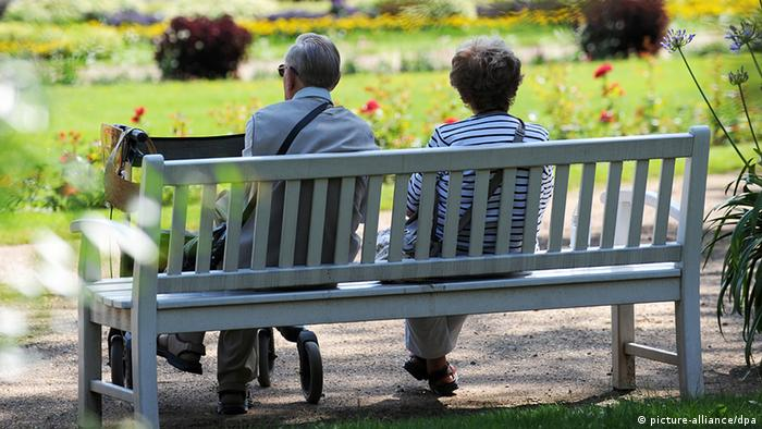 Elderly couple sitting on a park bench