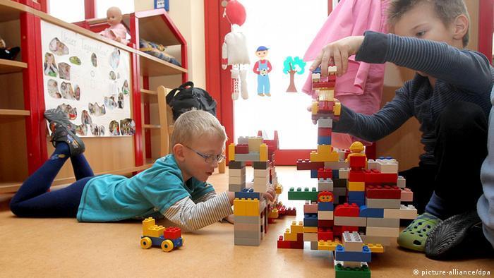 Zwei kleine Jungen bauen mit Lego einen Turm.