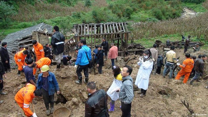 Rescuers search for victims after a landslide engulfed a building of a primary school at Zhenhe village (Photo: Reuters)