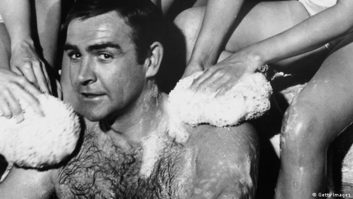 Connery sitzt in einer Badewanne und wird von Frauenhänden eingeschäumt