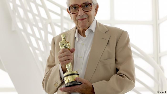 Ken Adam mit schwarzer Brille hält den Oscar in den Händen.