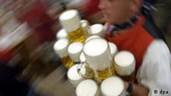 A waiter at Oktoberfest holds a number of glasses of beer as guests whizz past in the background