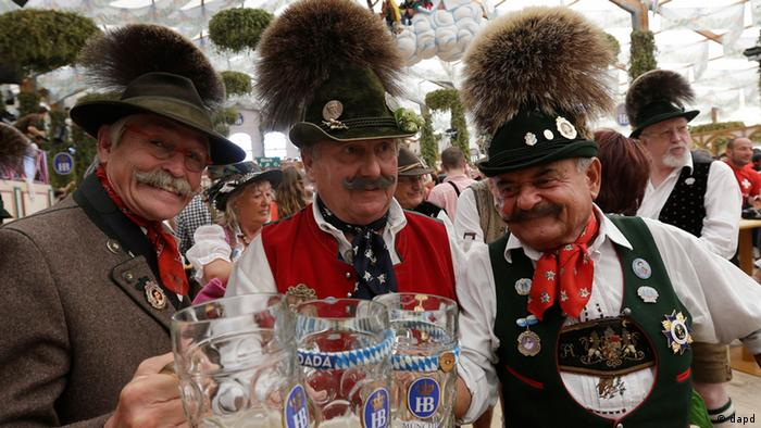Traditionally dressed Bavarian men raise their steins and enjoy a sunny day of the famous Bavarian Oktoberfest beer festival in Munich, southern Germany, Tuesday, Sept. 25, 2012. The world's largest beer festival, to be held from Sept. 22 to Oct. 7, 2012 will see some million visitors. (Foto:Matthias Schrader/AP/dapd)
