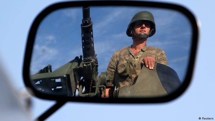 A Turkish soldier is reflected on a mirror as he stands guard on top of an armored personnel carrier on the Turkish-Syrian border near the Akcakale border crossing Photo: REUTERS/Murad Sezer