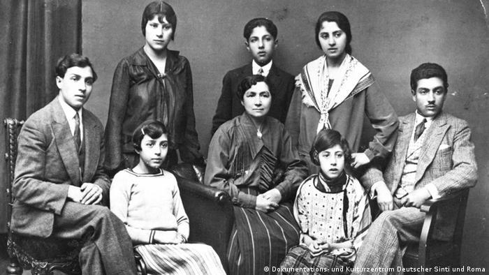 Schwarz-Weiß-Foto einer achtköpfigen Familie in guter Kleidung: Die Männer und Jungen tragen Anzüge und Krawatten, die Frauen und Mädchen Röcke und Blusen. Fünf Personen sitzen, drei stehen, alle schauen konzentriert nach vorne