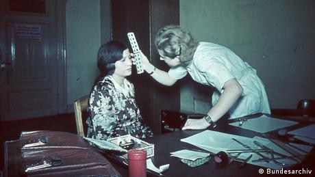 A woman measures another's face