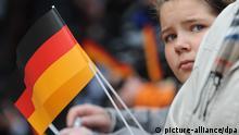 Ein kleines Mädchen mit einer Deutschlandfahne steht am Sonntag (03.10.2010) während der Feierlichkeit auf dem Marktplatz vor dem Rathaus in Bremen. Bremen ist Gastgeber der Jubiläumsfeiern zum Tag der deutschen Einheit, weil es zurzeit den Vorsitz im Bundesrat hat. Foto: Peter Steffen dpa