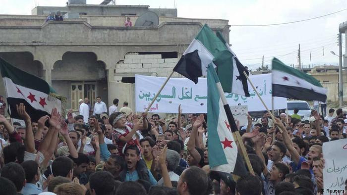 Demonstranten mit Flaggen der Opposition in Houla nahe Homs (Foto: rtr)