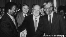 Treffen der Spitzenpolitiker Südafrikas: Mangosuthu Buthelezi (l) von der Inkatha-Freiheitspartei (IFP) gibt ANC-Führer Nelson Mandela (r) die Hand, während Frederik de Klerk (M) von der Nationalen Partei (NP) der Szene zuschaut (Archivbild vom 19.04.1994). Knapp zwei Jahre nach dem Ende des Apartheid-Regimes durch die Wahlen im April 1994 hat Nelson Mandela die politischen Zügel gegenüber der einst mächtigen Rechten spürbar angezogen und geht Konflikten mit seinem wenig geliebten Koalitionspartner de Klerk nicht mehr aus dem Wege. (Zu dpa-Korr.-Bericht Die politische Rechte in Südafrika hat abgewirtschaftet vom 24.01.1996)