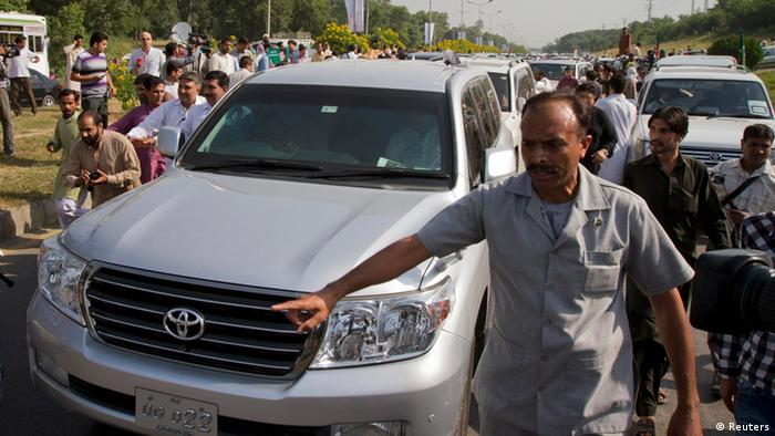 A security official escorts a vehicle carrying Imran Khan, cricketer-turned-politician and head of Pakistan Tehreek-e-Insaf (PTI) as he leads a peace march against U.S. drone strikes from Islamabad to South Waziristan on October 6, 2012. About 1000 PTI supporters including U.S. peace activists took part in a peace march which started on Saturday from Islamabad and due to reach South Waziristan on Sunday, according to local media. REUTERS/Faisal Mahmood (PAKISTAN - Tags: POLITICS CIVIL UNREST)
