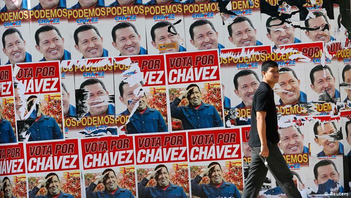 A man walks past campaign posters of Venezuelan President Hugo Chavez in Caracas October 6, 2012. Venezuelans go to the polls on October 7 in a presidential election that pits President Hugo Chavez against opposition rival Henrique Capriles. While most polls indicate a clear win for Chavez, others have shown Capriles narrowing the gap. Chavez is seeking a new six-year term as he marks his 14th year in power. REUTERS/Jorge Silva (VENEZUELA - Tags: POLITICS ELECTIONS)