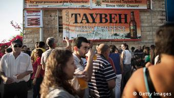 Palestinians and foreign visitors gather at the 2012 Taybeh Oktoberfest beer festival in the West Bank Christian village of Taybeh, Copyright: MARCO LONGARI/AFP/GettyImages