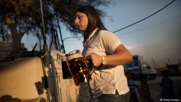 A Palestinian woman carries mugs of beer during the 2012 Taybeh Oktoberfest beer festival in the West Bank Christian village of Taybeh, near Ramallah, Copyright: MARCO LONGARI/AFP/GettyImages
