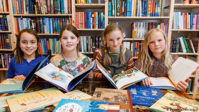 Vier Mädchen mit Kinderbüchern vor einer Bücherwand.