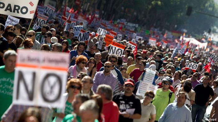 People hold banners against cuts during a demonstration in Madrid (AP Photo/Alberto Di Lolli)
