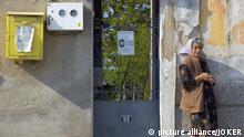 Svilengrad. Grenzstadt im Dreilaendereck Bulgarien/ Tuerkei/ Griechenland: Alte Frau vor ihrem Haus. Am Tor eine Todesanzeige der Familie. Swilengrad , Thrakien, Bulgarien, 04.05.2006 pixel