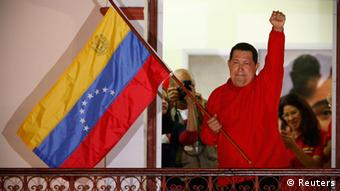 Venezuelan President Hugo Chavez waves the national flag while celebrating from a balcony at Miraflores Palace in Caracas October 7, 2012. Venezuela's socialist President Chavez won re-election in Sunday's vote with 54 percent of the ballot to beat opposition challenger Henrique Capriles. REUTERS/Jorge Silva (VENEZUELA - Tags: POLITICS ELECTIONS)